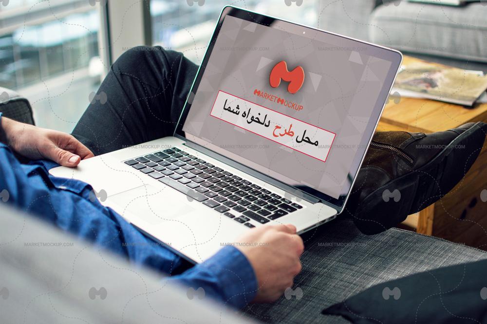 دانلود موکاپ لپ تاپ روی پاهای یک مرد